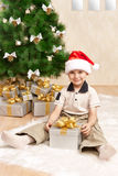 Child under the Christmas tree with gifts Royalty Free Stock Image