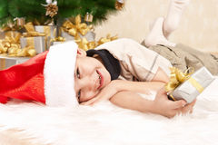 Child under the Christmas tree with gifts Royalty Free Stock Photo