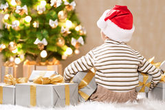 Child under the Christmas tree with gifts Stock Image