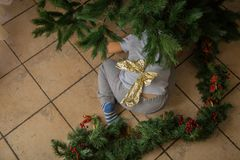 Child under Christmas tree with gold bow. Hidden away with background Stock Photos