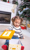 Child under the Christmas tree near the fireplace opens gift. Stock Photo