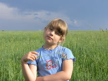 A child under dark storming sky. Single child in the endless meadow under dark storming sky Stock Images