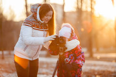 Child under supervision of mother pushing button of camera mounted on tripod Stock Photos