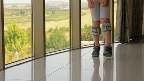 Child is under treatment with functional electrical stimulation. Slow motion shot of a child walking along the panoramic window indoor. Boy making the way under stock footage