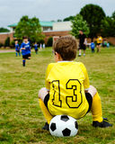 Child in uniform watching soccer game Royalty Free Stock Photography