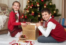 Child unpack gift boxes near christmas tree, decoration at home, happy emotion, winter holiday concept Stock Photos
