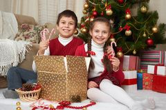 Child unpack gift boxes near christmas tree, decoration at home, happy emotion, winter holiday concept Stock Photography