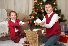 Child unpack gift boxes near christmas tree, show a handful of snow, decoration at home, happy emotion, winter holiday concept Royalty Free Stock Photography