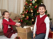 Child unpack gift boxes near christmas tree, show a handful of snow, decoration at home, happy emotion, winter holiday concept Royalty Free Stock Images