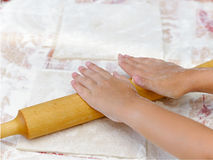 Child unrolls dough with  rolling pin. Baking Christmas cookies, child hands cuts dough Royalty Free Stock Photo
