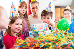 Child unwrapping birthday gift with friends. At home birthday party, mom is helping Royalty Free Stock Photos