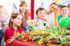 Child unwrapping birthday gift with friends. At home birthday party, mom is helping Stock Photo