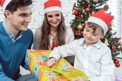 Child unwrapping Christmas present with his family. Being excited Stock Photos