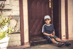 Child boy punished sad boring sitting lonely on door steps stock photography