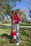 Child upside down hanging from mother hands. Three years old blonde child laughing face, upside down, hanging from women mother hands, playing on green grass Royalty Free Stock Image