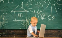 Child use laptop to get access to online education. Little boy learn online in computer class at school. Get more out of. Now royalty free stock photo