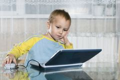 Child uses a children`s game computer Royalty Free Stock Images