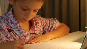 Child uses tablet for homework, girl writing for school in night internet usage 4K stock footage