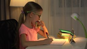 Child Uses Tablet For Studying, Girl Writing Homework in Night Internet Usage 4K.  stock footage