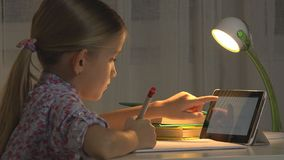 Child Uses Tablet Studying, School Girl Writing Homework in Night Internet Usage royalty free stock photo