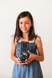 Child using camera. A pretty girl using an old film camera Royalty Free Stock Photos