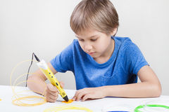 Child using 3d drawing pen. Creative, technology, leisure, education concept. Kid using 3d printing drawing pen. Creative, leisure, technology education concept Stock Image