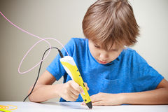 Child using 3D printing pen. Boy making new item. Creative, technology, leisure, education concept. Child using 3D printing pen. Boy making new item. Creative Royalty Free Stock Photo