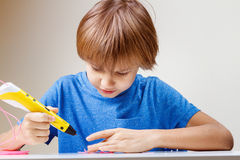 Child using 3D printing pen. Boy making new item. Creative, technology, leisure, education concept Royalty Free Stock Photos