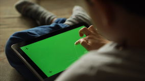 Child using a digital tablet PC with green screen