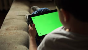 Child using a digital tablet PC with green screen, back view stock footage
