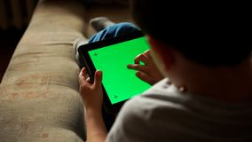 Child using a digital tablet PC with green screen Royalty Free Stock Photography