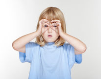 Child using fingers as binaculars Stock Images