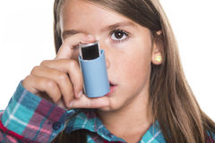 Child using inhaler for asthma. White background. A child using inhaler for asthma. White background studio picture royalty free stock photo