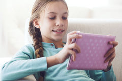 Child using ipad. Preteen school girl of 8-9 years old playing on ipad tablet pc at home Stock Photo