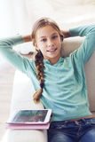 Child using ipad. Preteen school girl of 8-9 years old playing on ipad tablet pc at home Stock Images