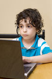 Hispanic child using a laptop at home. A child using a computer at home. Youth and technology concept. Playing electronic and online games. Latin boy with curly royalty free stock photo