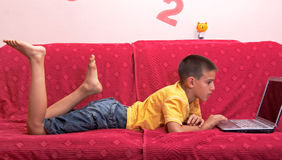 Child Using Laptop. Little boy looking above laptop screen Royalty Free Stock Photos