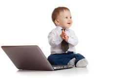 Child using a laptop and clapping his hands. Baby boy using a laptop Royalty Free Stock Photos
