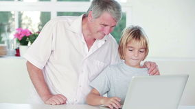 Child using a laptop with his grandpa Stock Photo