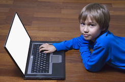 Child using laptop PC lying on wooden floor. Top view. Education, learning, technology concept Stock Images