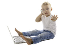 Child using a mobile phone and laptop Stock Images
