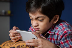 Child using a smart-phone with funny expression. Royalty Free Stock Images