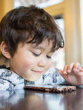 Child using smartphone. Young boy using a smartphone as entertainment Stock Photography