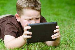 Child using tablet computer. Outdoors Royalty Free Stock Photography