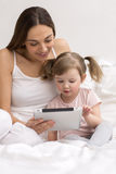 Child using tablet with her mother Royalty Free Stock Image