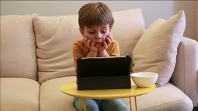 Child using tablet pc on bed at home. Cute boy on sofa is watching cartoon, playing games and learning from laptop. Education, fun stock footage