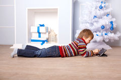 Child using tablet PC. Computer Generation concept. Happy child using a tablet PC near the Christmas tree and fireplace. Computer Generation concept Stock Images