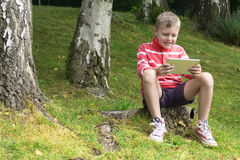 Child using the tablet. Sitting on a lawn in autumn Royalty Free Stock Photos