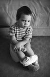Child using toilet. Looking thoughtful; bw film scan showing grain Stock Photo