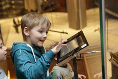 Child using touch screen. In a museum Stock Photography